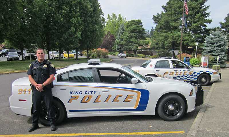 by: BARBARA SHERMAN - SNAZZY LOGO SUITS NEW VEHICLES - King City police officer Aaron Codino stands in front of one of two new police cruisers; the older one that will remain in service for a while is in the background.
