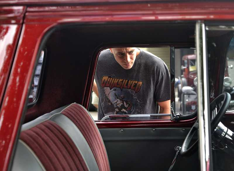 by: RAY HUGHEY - Nick Yazzolino, of Portland, checks out a 1957 Chevy entry owned by Ron Roberts, of Woodburn.