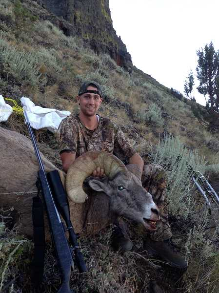 by: SUBMITTED  - Wilsonville's Brandon Aufenthie recently stalked and killed this sizable bighorn sheep on top of the Abert Rim in Lake County in southern Oregon. His shot measured 338 yards.