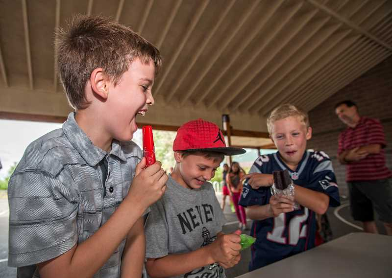 by: JOSH KULLA - Boones Ferry Primary School fourth-graders, from left, Hunter Turner, Austin Lowery and Evan Storm enjoy popsicles Thursday at a back-to-school event.