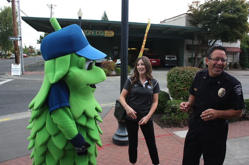 by: HILLSBORO TRIBUNE PHOTO: DOUG BURKHARDT - Hillsboro Police Department Lt. Mike Rouches enjoys some levity with Hops mascot Barley and Ariel Wagner, director of community relations for the Hillsboro Hops organization, before Barley began serving as a pedestrian decoy in a police safety activity at the corner of Lincoln Street and Third Avenue in downtown Hillsboro.