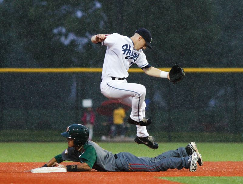 by: HILLSBORO TRIBUNE PHOTO: CHASE ALLGOOD - Hillsboro Hops shortstop Ryan Gebhardt jumps over Boise's Carlos Penalver during Monday night's Northwest League baseball game.