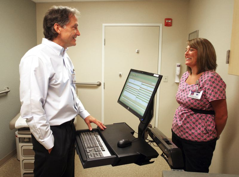 by: OUTLOOK PHOTO - Dr. Jon Hobson talks with medical assistant Jamie Austinson.