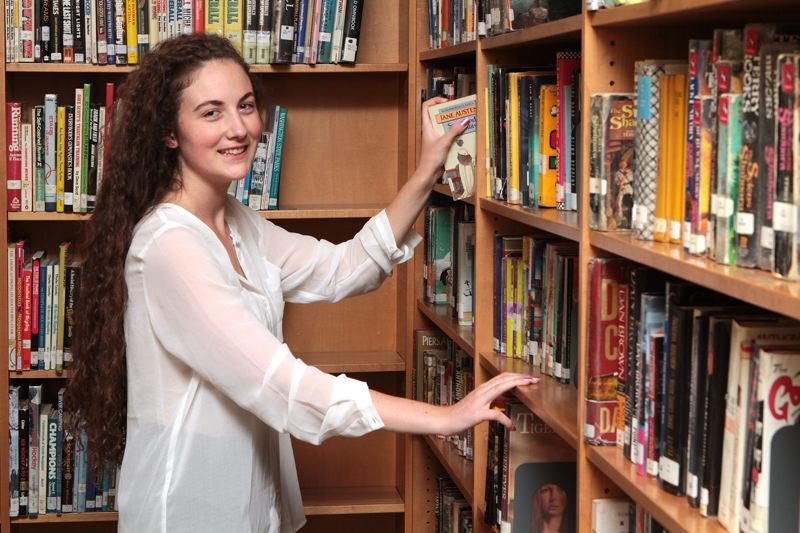 by: DAVID F. ASHTON - Cleveland High School National Merit Scholar graduate Mackenzie A. Broderick of Eastmoreland spends a moment in the schools library.