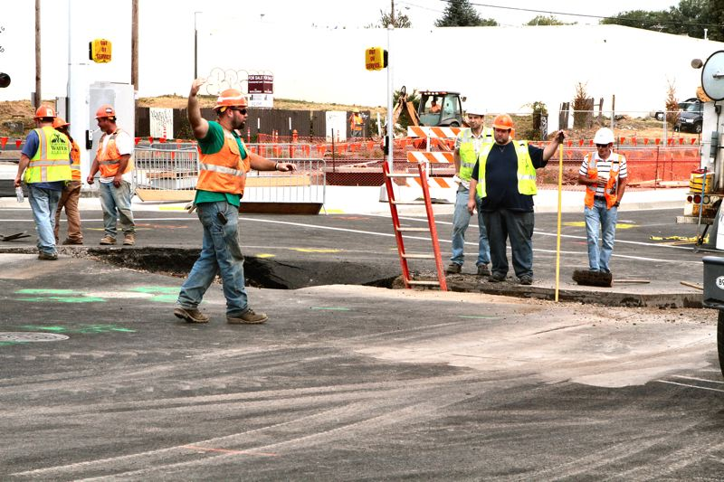 by: DAVID F. ASHTON - Portland Water Bureau crews get ready to ladder down into the street, to replace the section of ruptured water pipe.