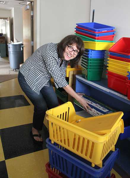 by: LINDSAY KEEFER - Amy Hanes, a kindergarten teacher at Gervais Elementary School, unpacks some belongings in her new classroom. School starts for grades K-8 in Gervais on Monday.