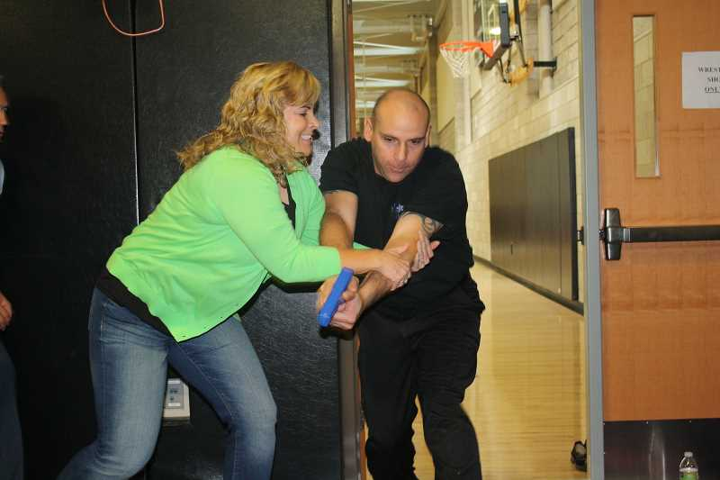 by: POST PHOTO: NEIL ZAWICKI - Naas Elementary School Educational Assistant Kristi Robertson learns to  surprise and tackle an armed intruder, portrayed by Sandy Police Officer Bill Wetherbee. The exercise was part of an Aug. 29 training session designed to teach educators to think like law enforcement officers.