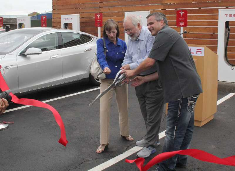 by: JEFF MCDONALD  - Marion County Commissioner Patti Milne, Rep. Phil Barnhart (D-Eugene), and Greig Olson of Elmers Restaurant cut the ribbon at Teslas new Supercharger site.