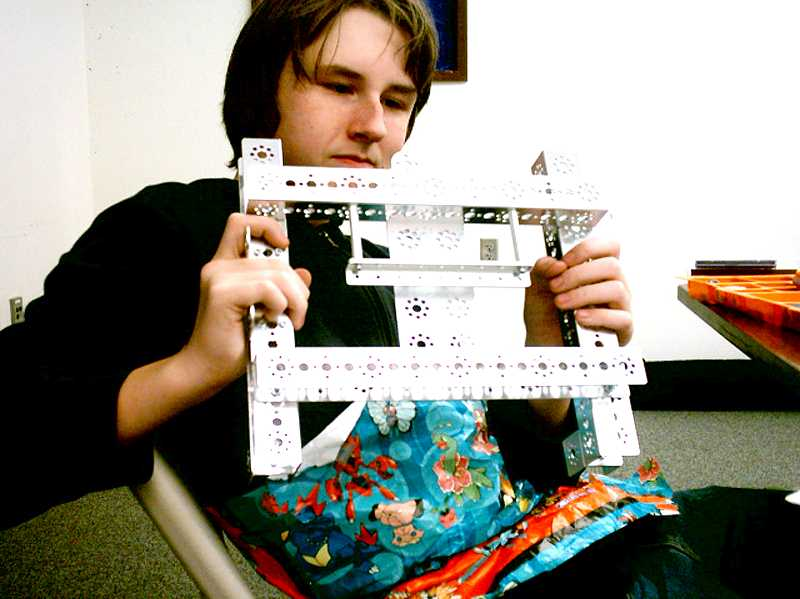 Spencer Roof, a Molalla High School student studies a section of his Robotics project