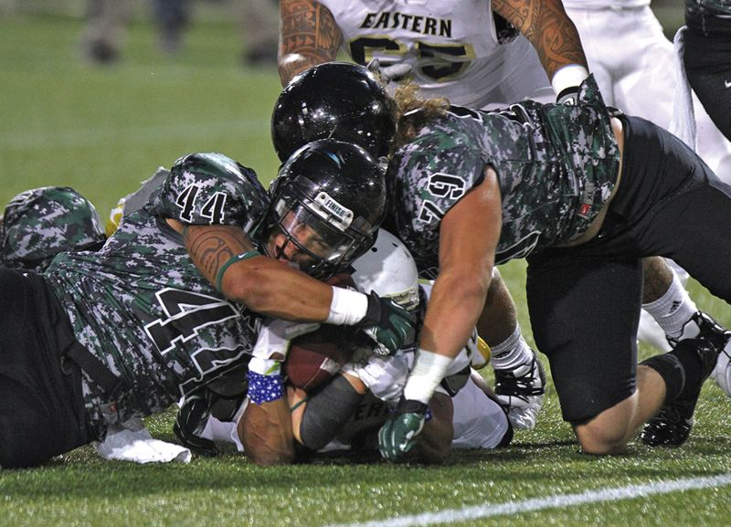 by: TRIBUNE PHOTO: JONATHAN HOUSE - Portland State defenders Brandon Brody-Heim (left) and Cutter Baldock bring down an Eastern Oregon ball carrier in the Vikings season opener at Jeld-Wen Field.