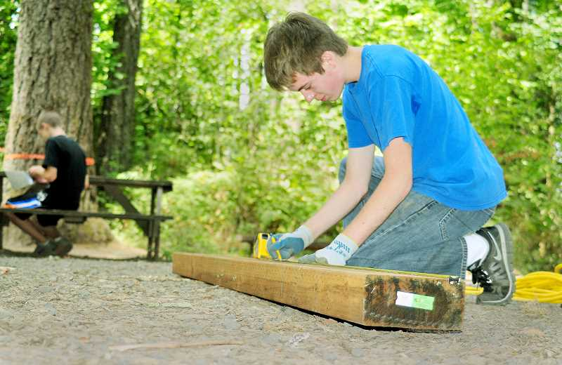 by: GARY ALLEN - Woodcraft - Cosmo Spada Jr. prepares timbers to be erected into benches at Tilikum Retreat Center last week.