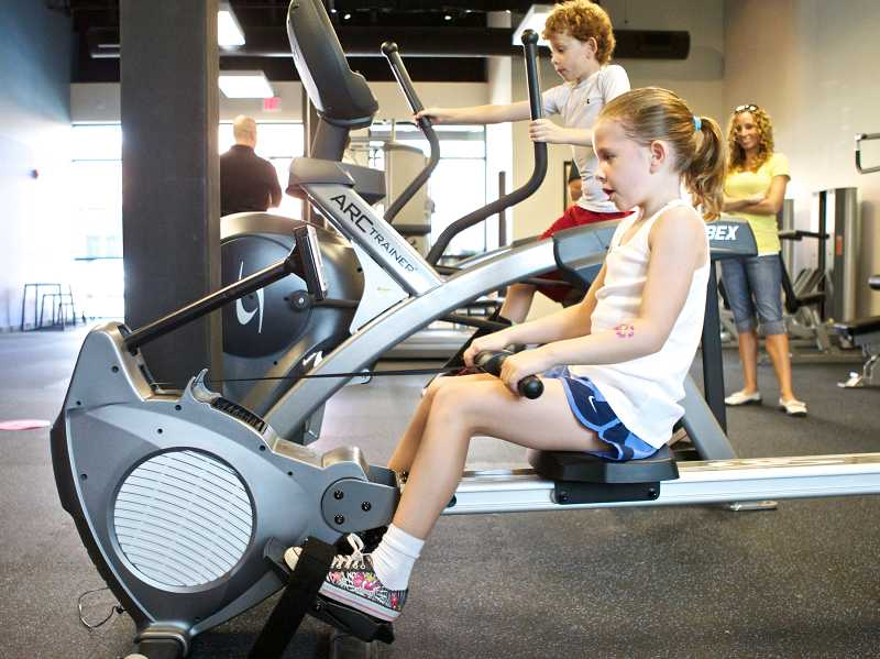 by: TIMES PHOTO: JAIME VALDEZ - Madelyn Crace, 7, and her older brother, Carson, 10, workout on a rowing and an elliptical machine at BIO Force Youth Fitness on Thursday.