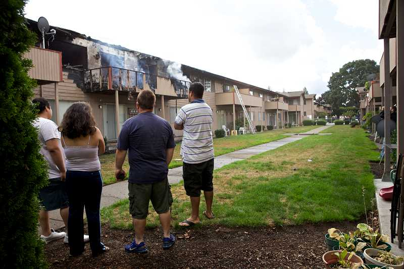 by: TIMES PHOTO: JAIME VALDEZ - Residents watch firefighters extinguish hot spots at the Country Oaks Apartments at 13795 S.W. Electric St.