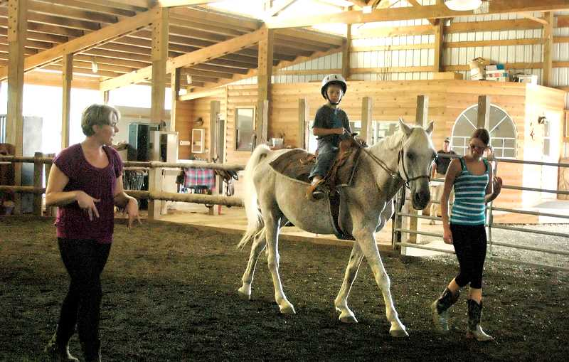 by: ISABEL GAUTSCHI - Barrett teaches Clayton Smiths second lesson. His mother said that Smiths first lesson was all he could talk about. He rides Senji, the senior Arabian horse. Kati Moyak assists.