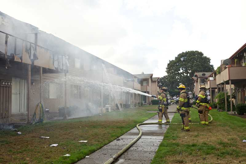 by: TIMES PHOTO: JAIME VALDEZ - TVF&R firefighters spray water on hot spots at the Country Oaks Apartments in Beaverton on Friday morning.
