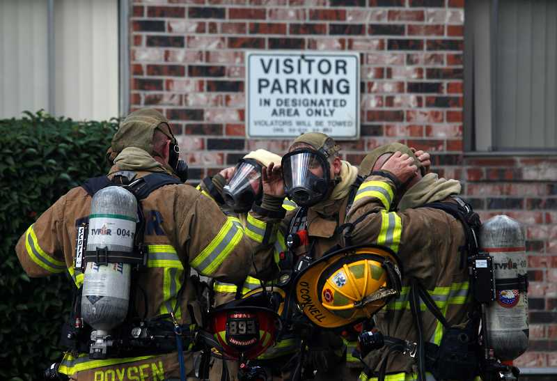 by: TIMES PHOTO: JONATHAN HOUSE - Tualatin Valley Fire & Rescue firefighters adjust their oxygen masks before entering a smoldering building at the Country Oaks Apartments.