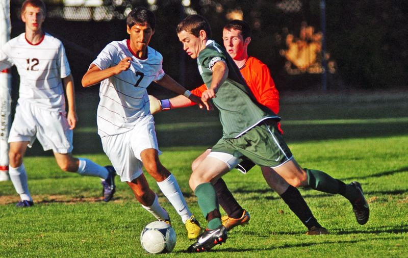 by: DAN BROOD - KICKING IT -- Tigard High School senior Sean McManamon, shown here in a match against Glencoe last year, is one of the key returnees for the Tigers this season. McManamon was an All-Pacific Conference first-team selection last year as a junior.