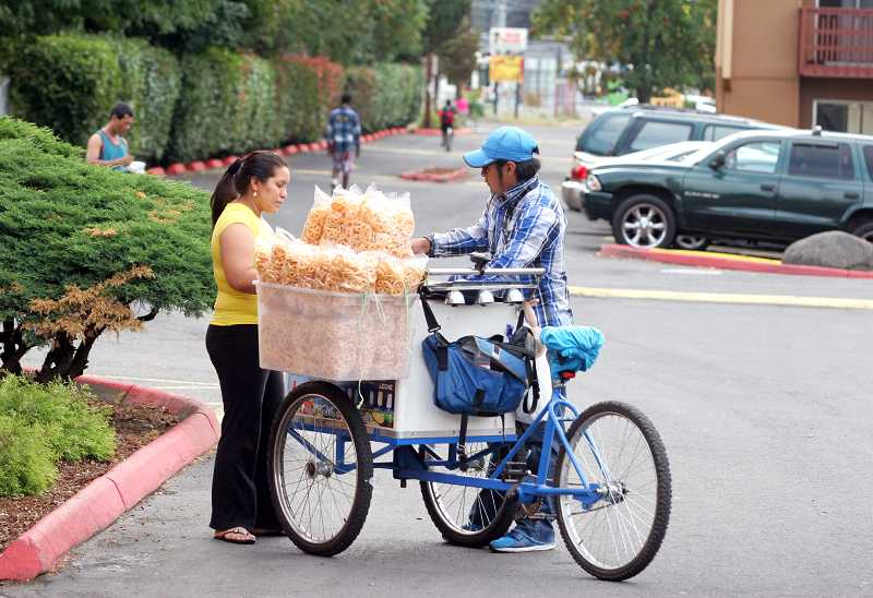 by: OUTLOOK PHOTO: JIM CLARK - VendorJesus Morales, right, sells churros to Barberry resident Juana Maria.