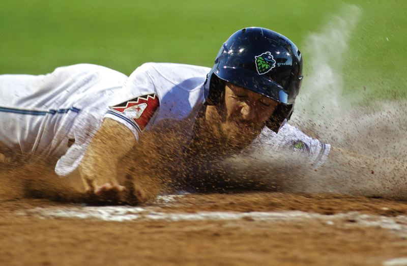 by: COURTESY PHOTO: CRAIG MITCHELLDYER/HILLSBORO HOPS - Hillsboro Hops centerfielder Taylor Ratliff gets a face full of dirt as he slides safely into home plate during the team's home finale last Friday against the Eugene Emeralds.