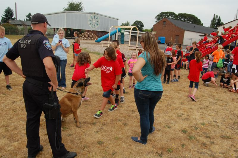 by: PHOTO BY: RAYMOND RENDLEMAN - OCPD Officer Dan Shockley allows students to pet Flint after introducing his canine partner at the Mt. Pleasant Elementary school field.
