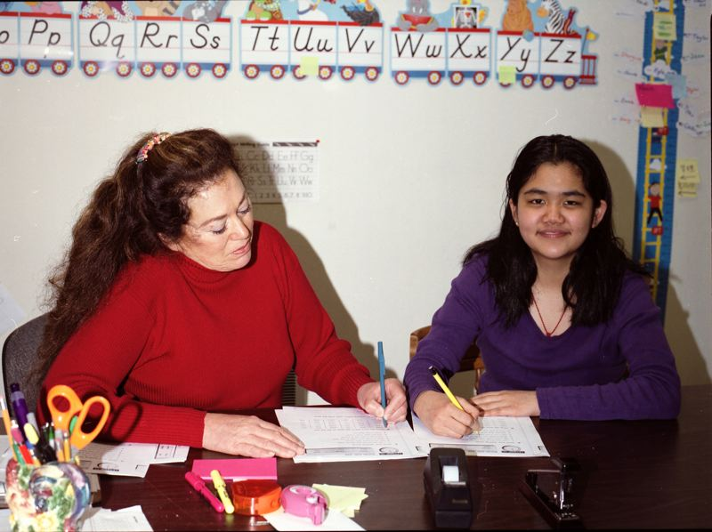 by: FILE PHOTO - Kitty Castro-Leon, founding executive director of the Neighborhood Learning Center in Clackamas, works with former student Tracy Ha.
