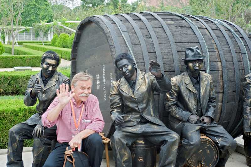 by: COURTESY OF JANIS MIGLAVS - Janis Miglavs poses for a photo with 'Tin Men' during the Wine Festival activities at Chateau Changyu-Castel, a joint venture winery in Yantai, Shandong Province, China.