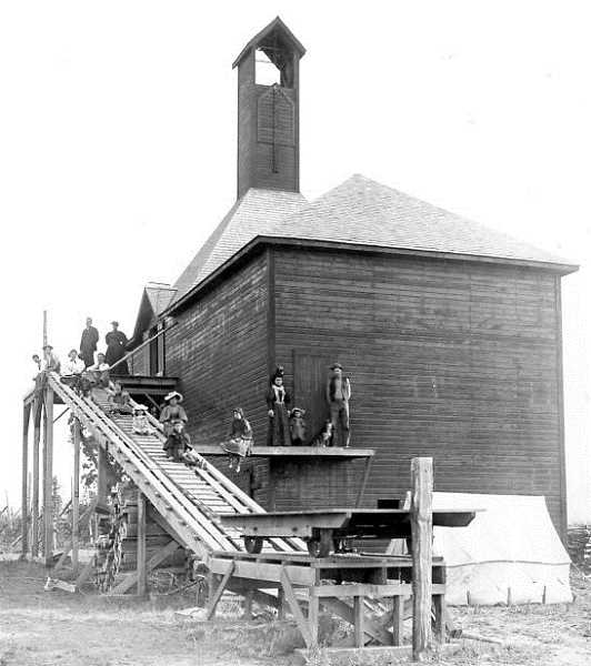 by: COURTESY OF DONNA GRAMSE - Local workers stand outside a hop dryer in this undated photo.