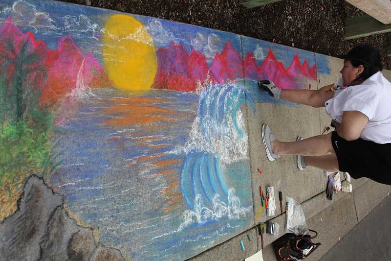 by: JEFF MCDONALD  - Gervais Mayor Shanti Platt designs a panoramic landscape design in chalk at the 4th annual Chalk Festival Saturday in Gervais.