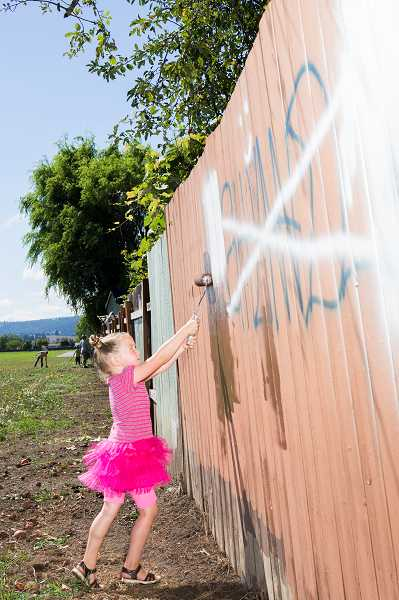 by: NEWS-TIMES PHOTO: CHASE ALLGOOD - MacKenzie Clark, 5, tried hard not to get her dress dirty as she painted over graffiti with other volunteers Saturday morning in Forest Grove. Clark is the daughter of Public Safety Advisory Commission member Allyn Clark, who helped organize the paintover party--and brought his parents along to help as well.