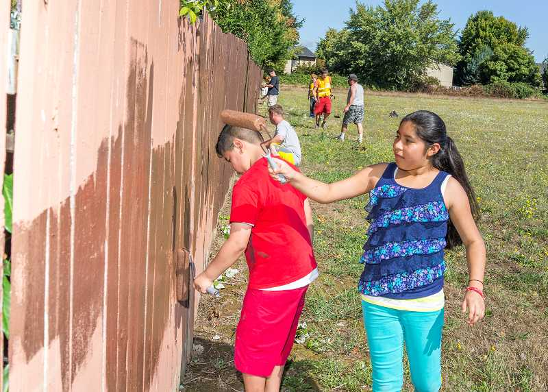 Yosellyn and Alex Rojas-Lopez grabbed paint rollers after they discovered volunteers painting over graffiti on the other side of their back fence. Their mother, Maria Lopez, and aunt, Celia Lopez, also joined the team of volunteers.