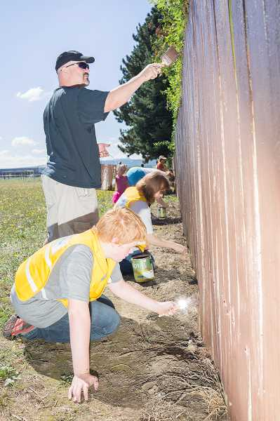 Public Safety Advisory Commission member Nathan Seable and his son, Quentin, work on repainting one section of the graffiti-covered fence. Seabolds other two sons also helped.