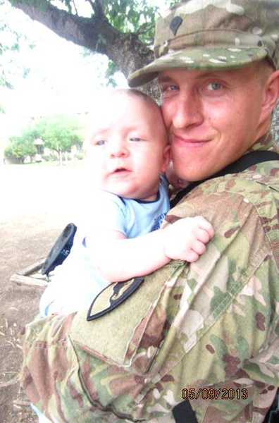 by: COURTESY PHOTO - Jason Walker holds his now 8-month-old son, Ryan, before his latest deployment to Afghanistan in May. Hes back on U.S. soil this week after stepping on an improvised explosive device.