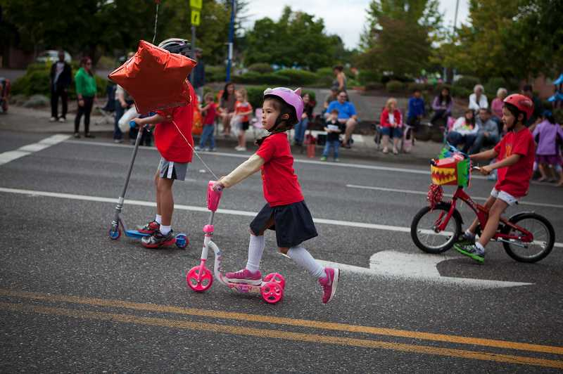 by: TIMES PHOTO: ADAM WICKHAM - A student from the Northwest Chinese Academy chose to ride a scooter along the route with her classmates.