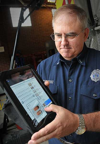 by: VERN UYETAKE - Emergency Medical Service Coordinator Steve DeHart of the Lake Oswego Fire Department demonstrates the amazingly versatile iPad used by his department.