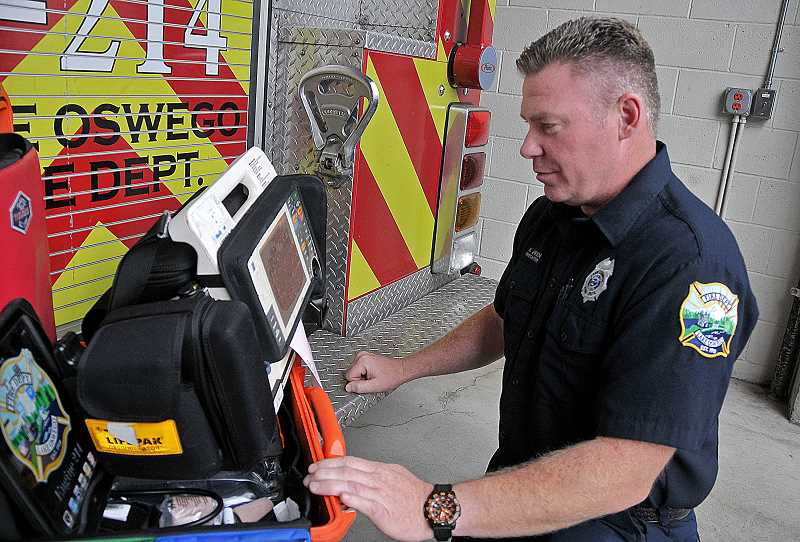 by: VERN UYETAKE - Firefighter Ken Green of the Lake Oswego Fire Department says of his department's defibrillator: 'We love this kind of stuff.'