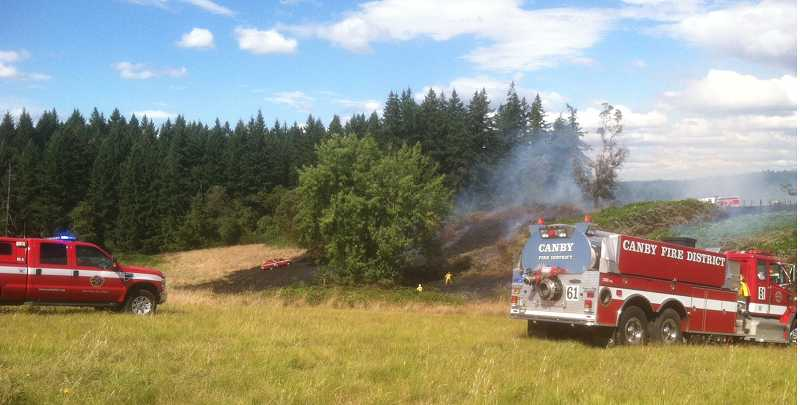 by: SUBMITTED PHOTO - Canby Fire District 62 firefighters battle a brush fire on Union Hall Road.