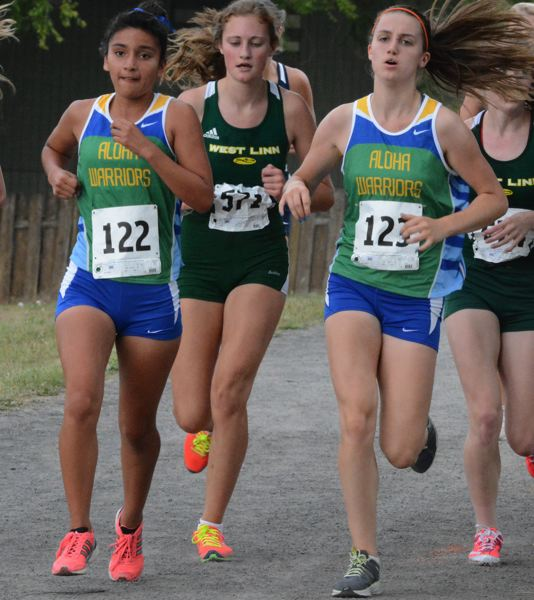 by: TIMES PHOTO: MATT SINGLEDECKER - Alohas Oralia Funez Mojica, left, and Sara Henderson, right, helped the Warriors have a standout showing at the Tualatin Invitational last Wednesday.