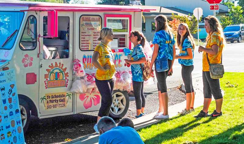 by: RAY HUGHEY - Customers line up for shave ice at the Kiss Summer Goodbye celebration.