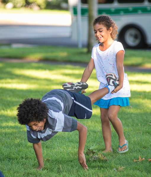 by: RAY HUGHEY - Isabell Taylor, 6, right, has fun wheelbarrowing Berik Winklebleck, 11, under the Wait Park trees.