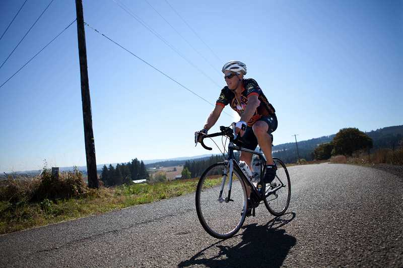 by: PHOTO FOR THE TIMES: ADAM WICKHAM - Ray Hennings of Aloha trains on Riedweg Road in the hills around Cornelius on Monday afternoon. Hennings will fly to South Carolina for a three-day, 220-mile bike trek to highlight kidney disease awareness.