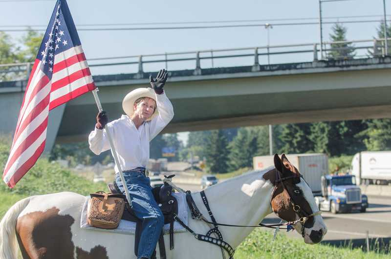 by: JOHN BAKER - Maggie Constantino sits astride her horse of 15 years, Cloud, enjoying the supportive honks and cheers from drivers along Interstate 5 Wednesday morning.