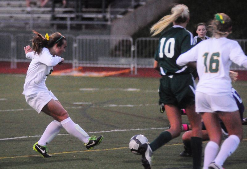 by: MATTHEW SHERMAN - West Linn's Cailey Scott knocks a shot under the hands of the Rex Putnam goalie for the first goal in Tuesday's game. The Lions would score the first three goals in an easy victory.
