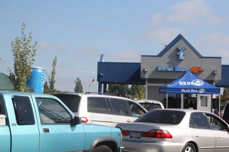 by: JEFF MCDONALD  - A steady stream of cars lined up to get $1 drinks at the new Dutch Bros. on the corner of Evergreen Road and Highway 214 in Woodburn Thurseday. All money from the Grand Opening day will be donated to the Woodburn School District.