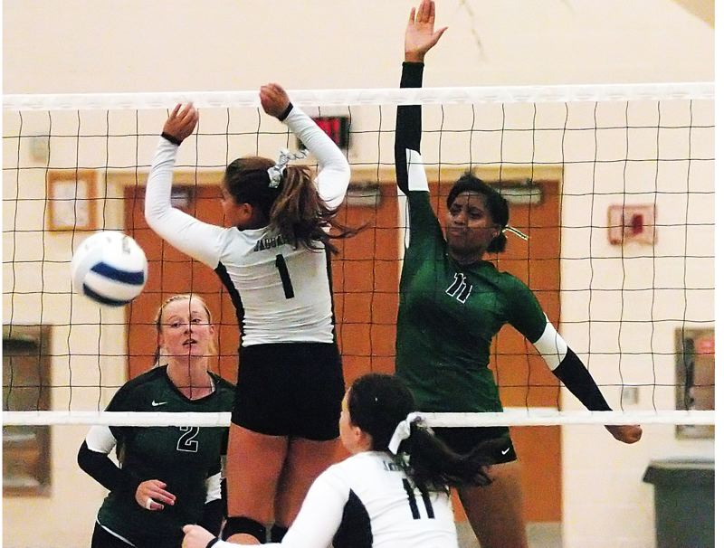 by: DAN BROOD - BIG BLOCK -- Tigard junior Sasha Hershey (11) goes up high at the net for a block during the Tigers' win at Century.