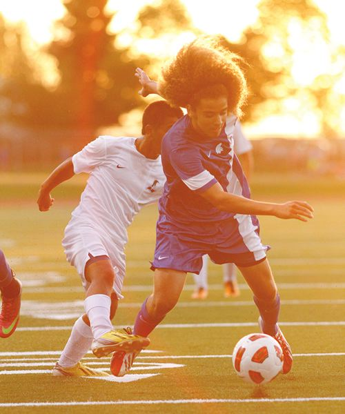 by: HILLSBORO TRIBUNE PHOTO: AMANDA MILES - An orange haze sets in during last Tuesday's non-league soccer match between Liberty and Hillsboro, while Hilhi's Tyler Hoiem controls the ball around a Liberty defender. The Spartans won the match 1-0 and have their sights on a top four finish in the Pacific Conference.