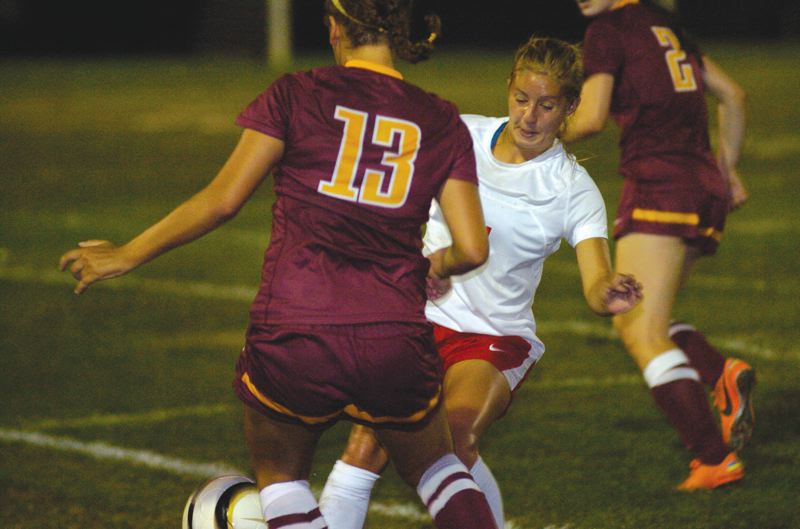 by: THE OUTLOOK: DAVID BALL - Centennials Lauren Lowrey charges in to stop a Central Catholic forward during the second half of Thursday nights 3-1 home win.