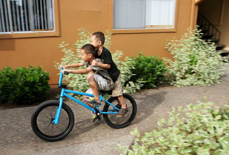 by: OUTLOOK PHOTO: JIM CLARK - Shaehlerpaw Shee, left, and his brother Hsartawshee Shee share a bicycle as they ride around the Barberry Village apartment complex.