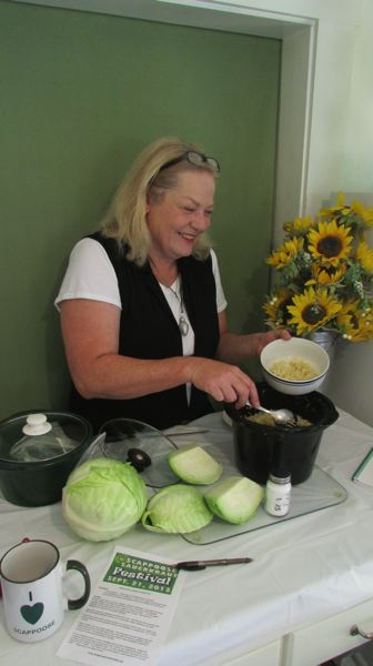 by: SPOTLIGHT PHOTO: DARRYL SWAN - Sauerkraut Festival organizer Lisa Smith demonstrates the ease and simplicity of making small batches of sauerkraut at home.