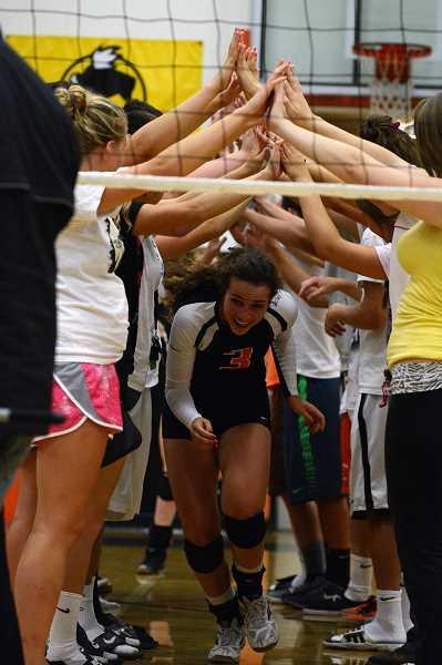 Senior Abby Kessi runs through the tunnel of fans as she is introduced before Thursday's game against Central. Scappoose won the first two sets and finished off the Panthers 3-1 on Sept. 12.