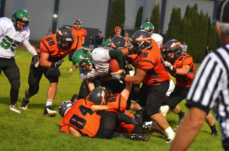 by: JOHN BREWINGTON - A swarm of Indian defenders tackle the ball carrier during Scappoose's 55-32 victory over Rainier on Friday night. Scappoose moves to 3-0 this season, and goes back on the road in week four.